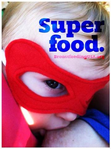 "A toddler wearing a superhero mask nurses. ""Super food."""